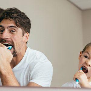Father a brushing teeth in bathroom.