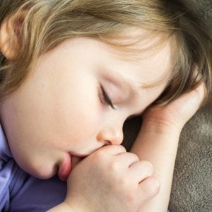 Young girl sucking her thumb in her sleep