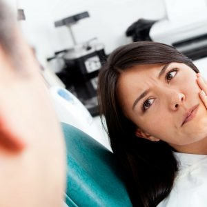 women at dentist suffering from tooth sensitivity