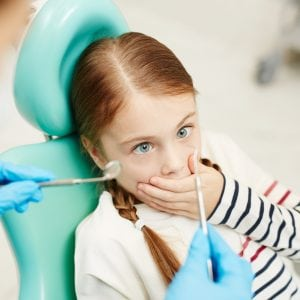 Scared little girl at the dentist
