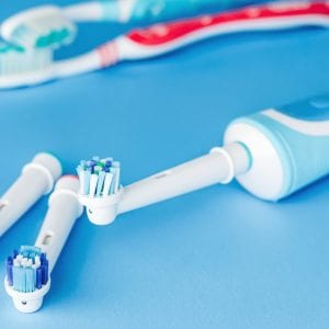 Electric and manual toothbrush on blue background, close up