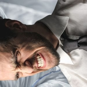 businessman clenching his jaw in bed