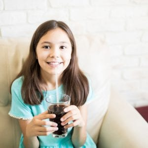 Cheerful young girl drinking soda drink with straw sitting on couch