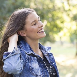 Portrait of happy smiling woman standing in the park on sunny summer or spring day outside cute smiling woman attractive young girl enjoying spring filtered image flare sunshine. Copy space
