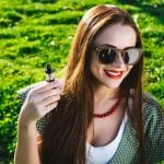 Happy fashion smiling Woman in sunglasses smoking vape on street, smoke