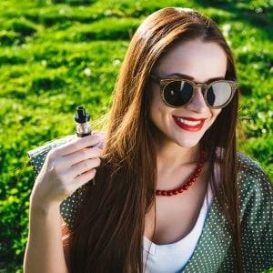 Happy fashion smiling Woman in sunglasses smoking vape on street, smoke